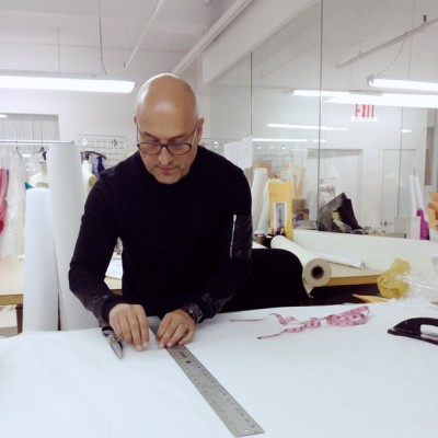 Before making a garment, Sanchez will sketch an idea, put together his ideal fabrics, and present the sketch to his team to create a canvas. Sanchez then cuts the fabric, drapes it over a mannequin, and moves to the table to transfer paper patterns.