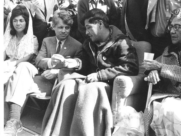 Robert F. Kennedy (middle) offers César Chávez (right) bread in a symbol of support at the end of Chávez's 1968 hunger strike for farm workers in Delano, CA.