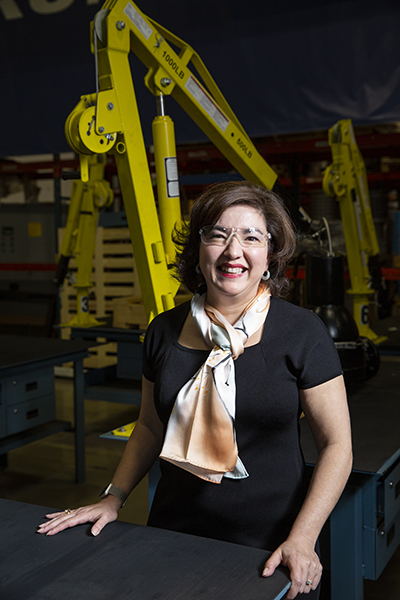 Rebecca O'Mara, Grundfos, seated in front of machinery, vertical image