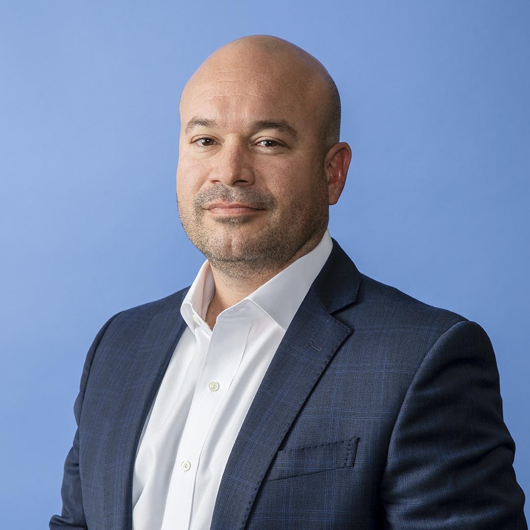 Ricardo Madan, TEKsystems, portrait blue background