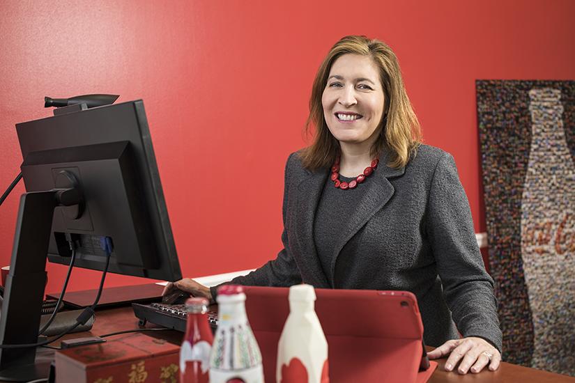 Beatriz Perez, SVP, Coca-Cola, at desk red background