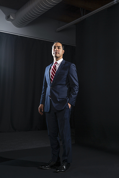 Julián Castro, standing, full-body image, industrial ceiling