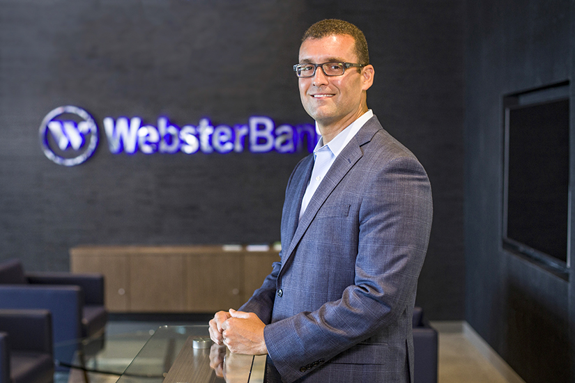 Jason Soto, Chief Credit Officer, Webster Bank, portrait by logo