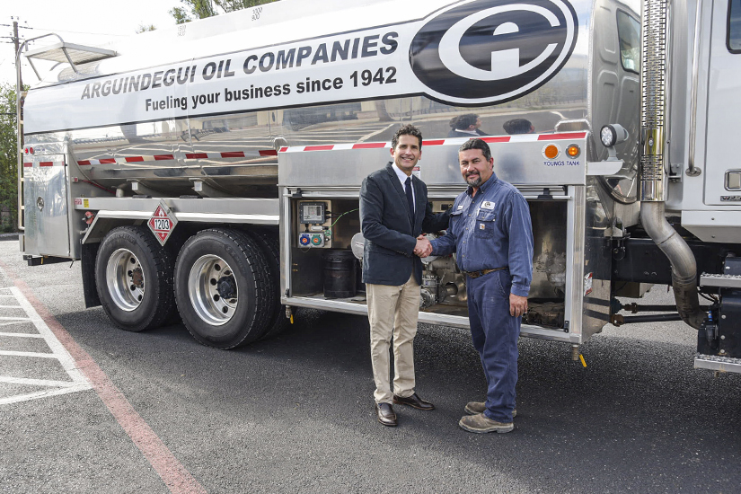 Alfonso Arguindegui Leyendecker shakign hands with employee in front of oil truck