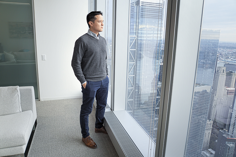 Alvaro Almanza, Kensho Technologies, looking out window of 76th floor office of Freedom Tower, Manhattan