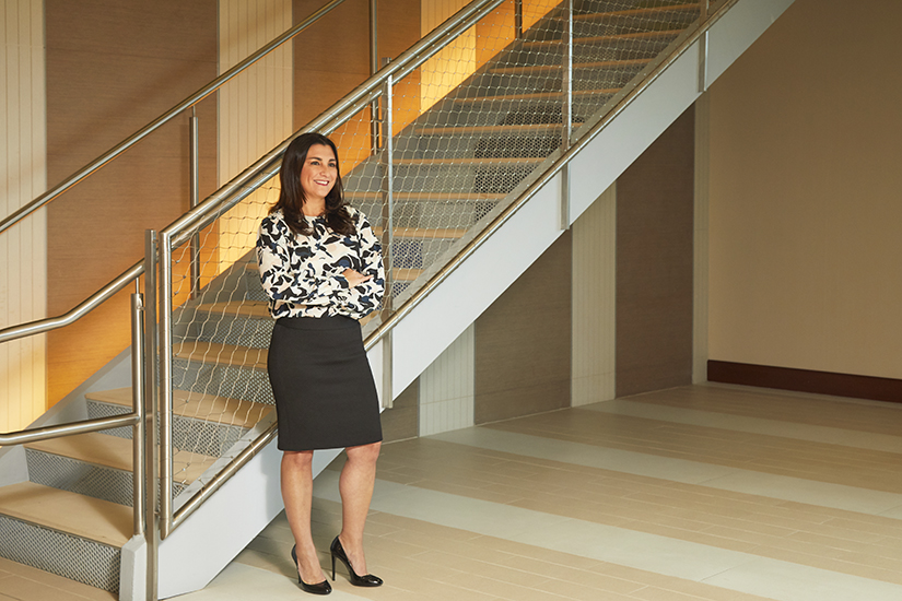 Ruth Giansante, World Fuel Services, portrait wide, standing by staircase