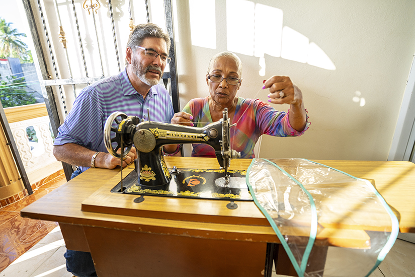 Albert Reyes and woman with sewing machine